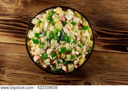 Salad With Crab Sticks, Sweet Corn, Cucumber, Eggs, Rice And Mayonnaise On Wooden Table. Top View