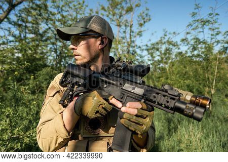 Airsoft Player In Military Uniform Holds A Weapon In His Hands