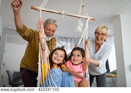 Grandchildren Having Fun At Home While Playing With Their Grandparents