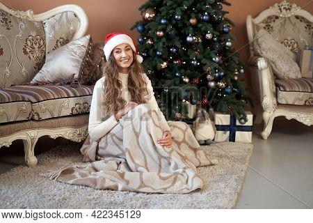 Christmas. Woaman Dressed White Sweater Santa Hat Sitting On The Floor Near Christmas Tree Wrapped H