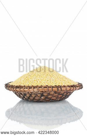Heap Of Millet Grains In A Wooden Plate. Isolated On White Background.