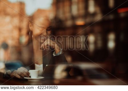 woman in a coffee shop drink coffee viewed through glass with reflections as they sit at a table chatting and laughing