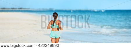 Running fitness on beach athlete runner running away doing high intensity interval training on summer workout. View from the back of woman panoramic.