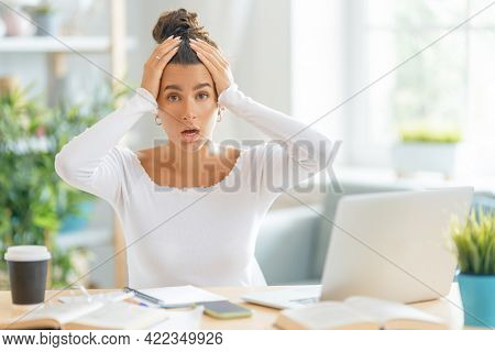 Young businesswoman studying online, watching webinar, podcast on laptop and having a head ache. E-learning concept.
