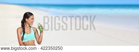 Fitness running woman drinking green smoothie juice bottle on beach landscape banner background. Healthy athlete active living on detox diet probiotic shake panoramic.