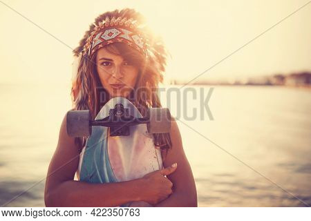 A beautiful young girl with indian war bonnet holding her skateboard and posing for a photo while enjoying beautiful sunset on the seaside. Summer, sea, vacation