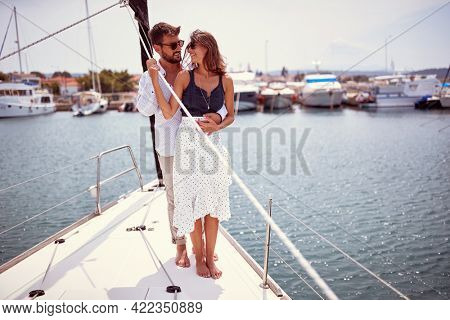 A young couple in love is standing in a hug on a yacht and spending romantic moments while riding through the dock on a beautiful summer day on the seaside. Summer, sea, vacation, relationship