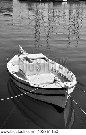 Small white fishing boat. Black and white photography. Heraklion, Greece