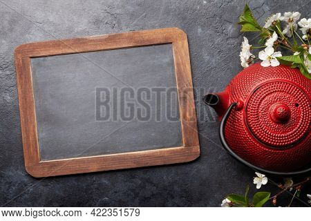 Japanese tea in tea pot and cherry blossom on stone table. Top view flat lay with chalkboard for copy space