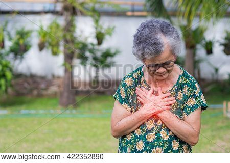 An Elderly Asian Woman Having Heart Attack. Senior Woman Clutching Her Chest In Pain At The First Si