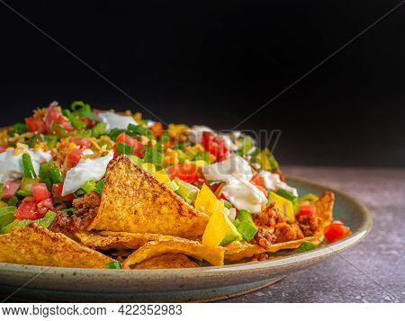 Side View Of Loaded Minced Pork Nachos On Plate With Black Wall Background. Space For Text. Concept