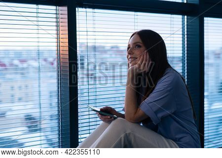 Happy Redhead Young Woman Dials Number And Speaks To Boyfriend Sitting On Windowsill In Evening Afte
