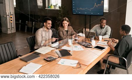 Colleagues Having Meeting In Boardroom, Working On Startup