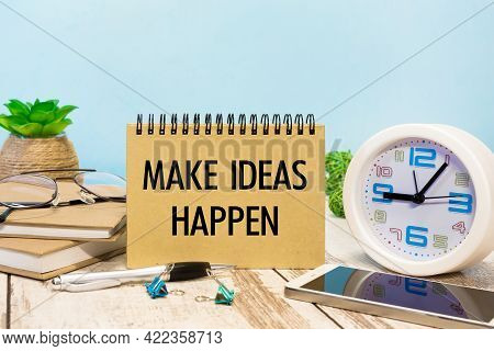 A Sign With The Inscription Make Ideas Happen On The Table With Office Supplies