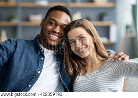 Portrait Of Cheerful Young Romantic Interracial Couple Taking Selfie Together At Home