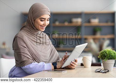 Smiling Muslim Woman Using Tablet Sitting At Desk