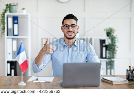 Online French Lesson. Foreign Languages Tutor Teaching Class On Web, Using Laptop Pc, Showing Thumb