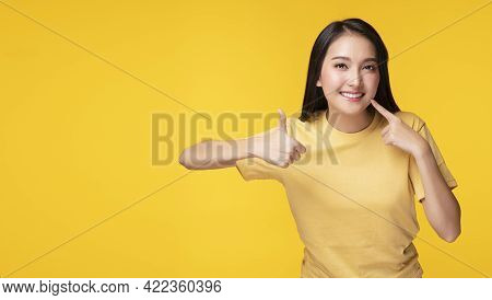 Dental Care And Healthy Concept. Cheerful Young Woman Using Finger Point To Her Whitening Teeth Whil