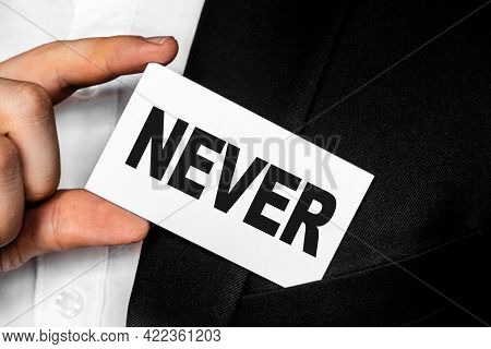 Inscription Never On A White Business Card. A Man In A Black Business Suit Lowers Or Removes From Hi