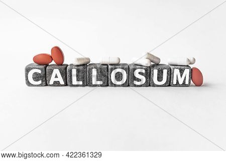 Callosum The Word On Stone Cubes. Cubes Stand On A White Surface, Many White And Red Pills. Medicine