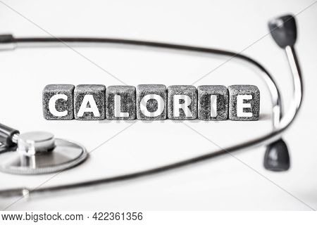 Stone Block Form Word Calorie With Stethoscope. White Background. Medical Concept. Unit For Measurin