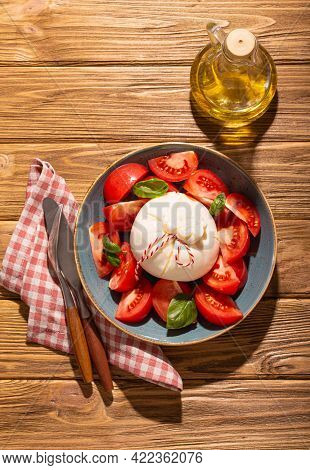 Italian Salad With Fresh Tomatoes, Burrata Cheese, Basil Served On Ceramic Plate With Bottle Of Oliv