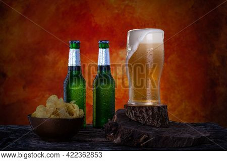 Glass Of Fresh Pint Beer With Foam Next To Two Green Bottles Of  Lager Beer.  Bottles And Glass With