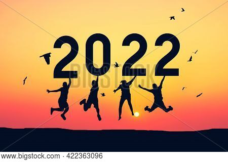Silhouette Friends Jumping And Holding Number 2022 On Sunset Sky Abstract Background At Tropical Bea