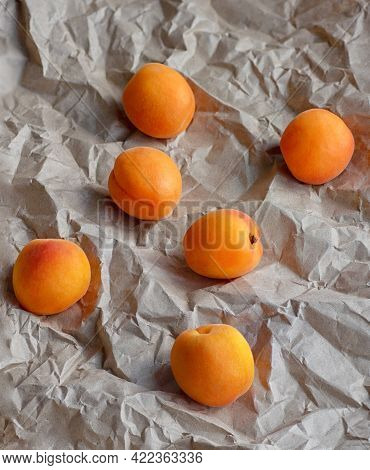 Ripe Juicy Apricots On The Background Of Crumpled Wrapping Paper. Vertical Crop. Close Up.