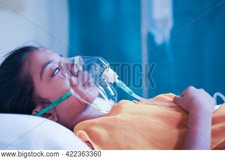 Side View Of Girl Kid Breathing On Ventilator Oxygen Mask Due To Coronavirus Covid-19 Breathing Shot