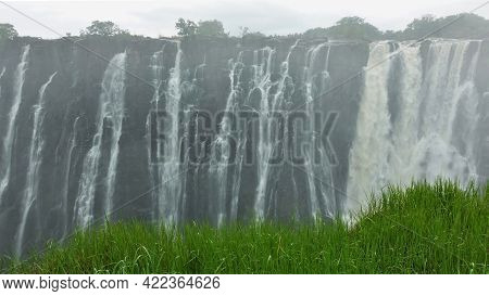 Unique Victoria Falls. Streams Of Water Plunge Into The Abyss. There Is Fog Over The Gorge. Lush Gre