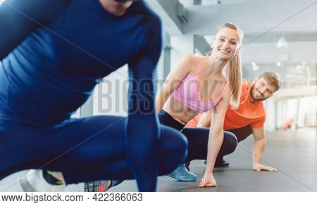 Group of people in gym fitness class stretching