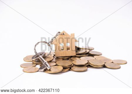 House Keys With House Shaped Keychain On Stack Money Coins, Isolated On White Background.