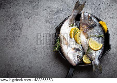 Raw Fresh Fish Sea Bream Or Dorado With Lemon, Thyme, Rosemary And Seasonings In Cast Iron Skillet F