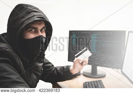 Cunning Hacker Fraudster In White Background With Stolen Credit Card In Hand Tries To Steal Money Fr