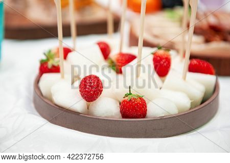 Catering service. Tasty appetizers on the table, melon and strawberries