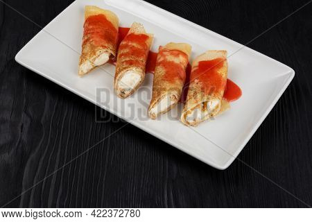 Pancakes or russian blini stuffed with cream sauce on a white plate.
