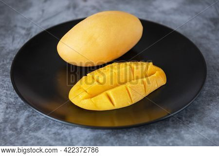 Fresh yellow mango fruit in a black plate on grey stone backgrounds