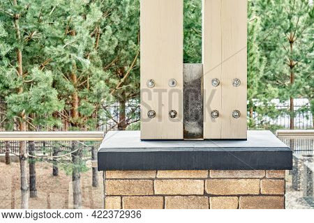 Support Of Wooden Poles For Roof Overhanging Above Terrace On Concrete Foundation Decorated With Bri