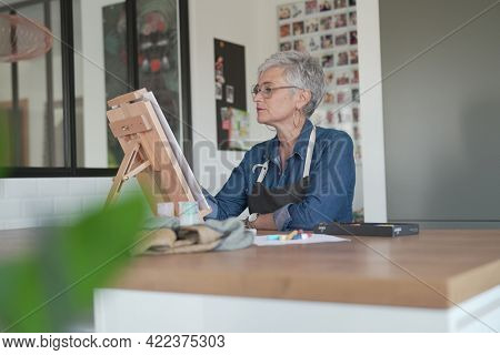 portrait of a 55 year old senior woman doing art painting
