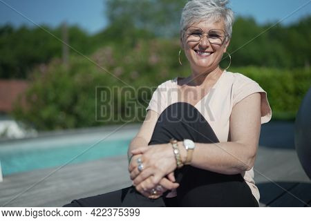portrait of a 55 year old senior woman doing fitness outside her house