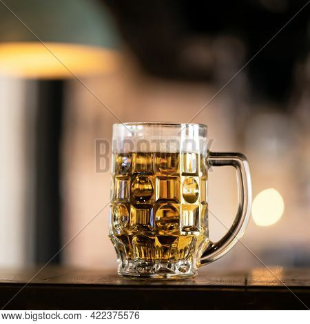 Glass Cup Of Chilled Light Beer With Froth. Alcoholic Beverage On Counters Of Brewery Against Of Bac