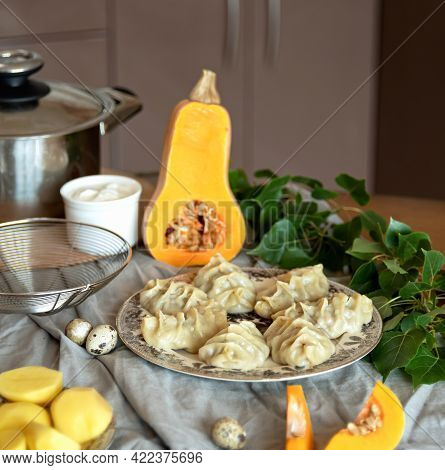 Dish Of Boiled Dumplings With Pumpkin And Potatoes On Tablecloth With Ingredients And Kitchen Utensi