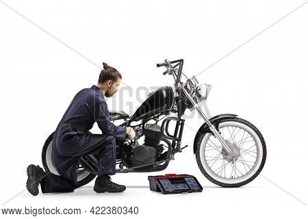 Motorcycle mechanic with a tool box repairing a chopper motorbike isolated on white background
