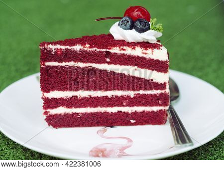 The Cake Is Cut Into Pieces With A Red And White Pattern With Cherries And Blueberries On Top.