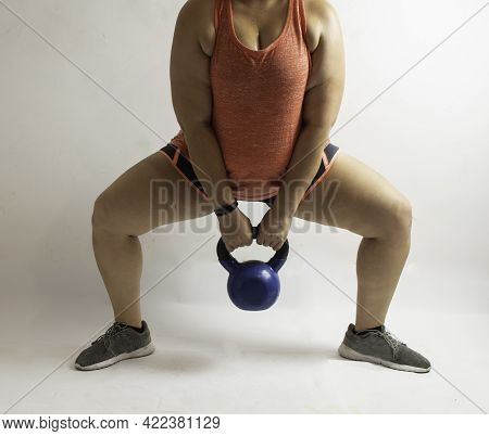 White Woman Performing Sumo Squat With Kettlebell On A White Background