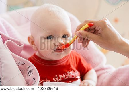 Breastfed Blonde Baby In A Red T-shirt Tries First Complementary Foods From A Small Red Spoon On A P