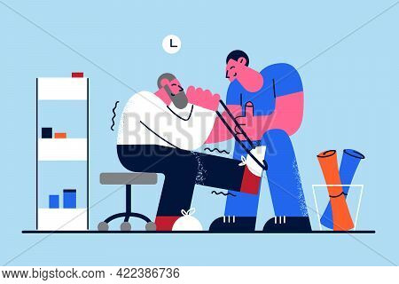 Rehabilitation Clinic And Healthcare Concept. Grey Haired Mature Man With Injured Leg Sitting And Ge