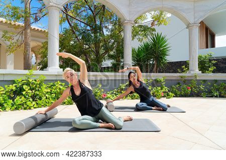 Two Beautiful And Happy Women In Sportswear With Smile Doing Yoga Or Stretching Exercises In Park On