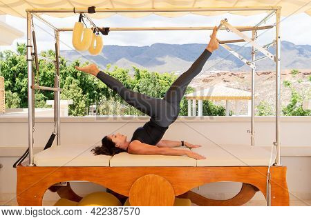 Flexible Woman Practicing Pilates On Summer Day On Special Equipment, Young Fitness Lady Stretching